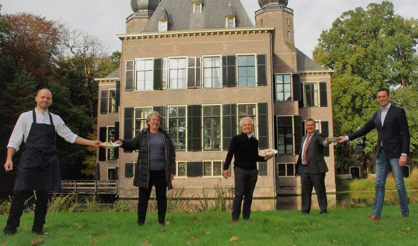 <p>Chef-kok Erik van der Hulst (l) en directeur Jan-Willem Besselink (tweede van rechts) van Oud Poelgeest overhandigen de eerste maaltijden aan Eveline Idema en Hugo Brouwer (Voedselbank Leiden), en Arthur van Elzelingen (r) (Voedselbank Teylingen). | </p>