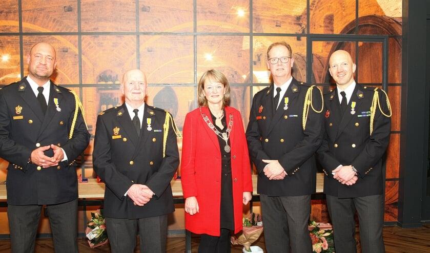 Burgemeester Spruit te midden van de vier Leden in de Orde van Oranje Nassau.