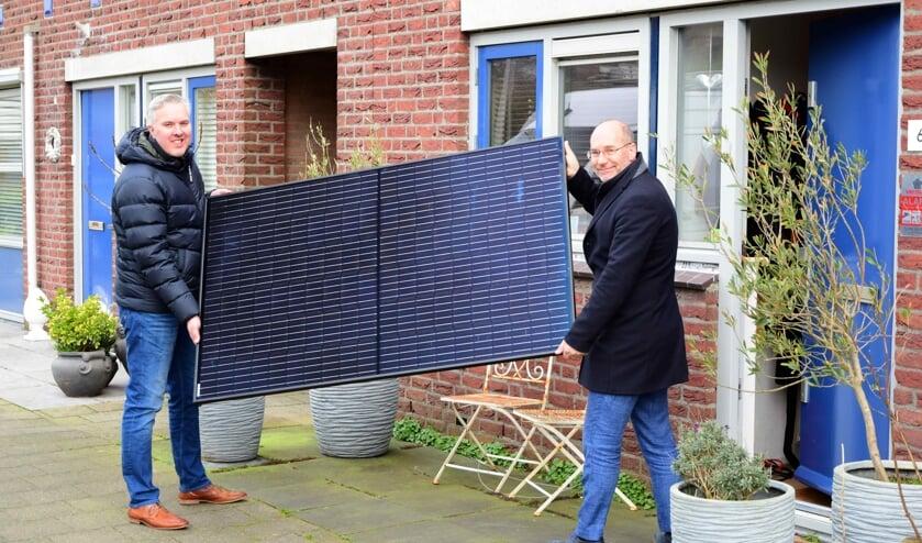 Johan van Buren (r) van Stek helpt deze huurder symbolisch een handje. Die laat zonnepanelen op het dak van zijn woning plaatsen.