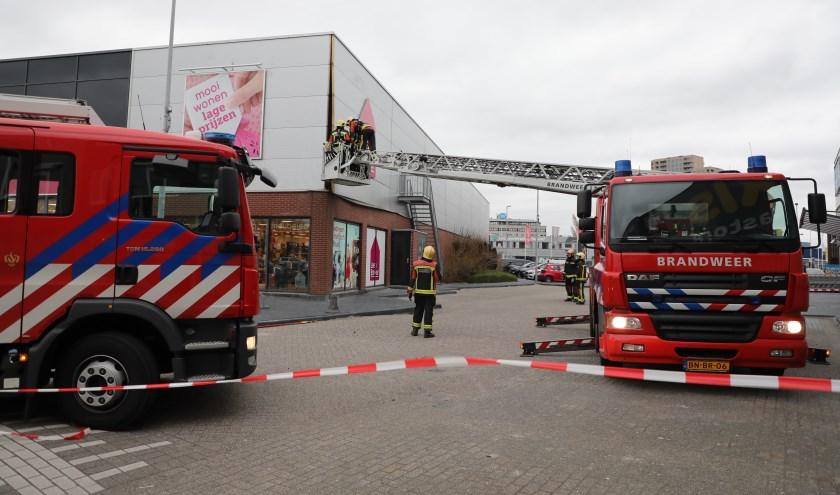 De brandweer probeert het losgewrikte geveldeel weer vast te zetten.