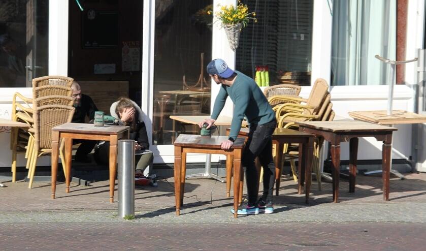 Personeel van De Rosser schuurt de terrastafels in afwachting van beter tijden. | Foto en tekst: Wim Siemerink