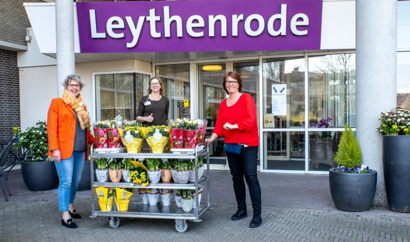 V.l.n.r. Rina Cooijmans van de Oranjevereniging Leiderdorp en Anja van Rijn en Marlèn Bohemen van het Uitbureau van Leythenrode bij de kar vol kleurige planten.