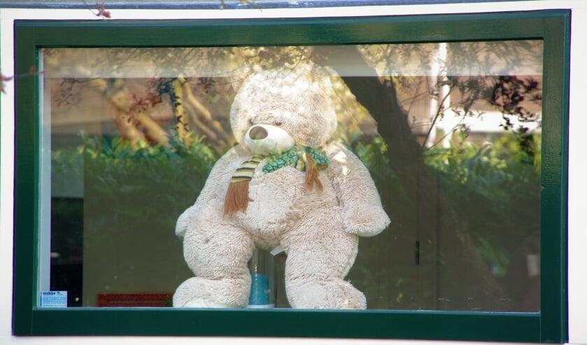 Een knuffelbeer kijkt aan de Oranjelaan nieuwsgierig naar buiten of er al kinderen langs wandelen.  
