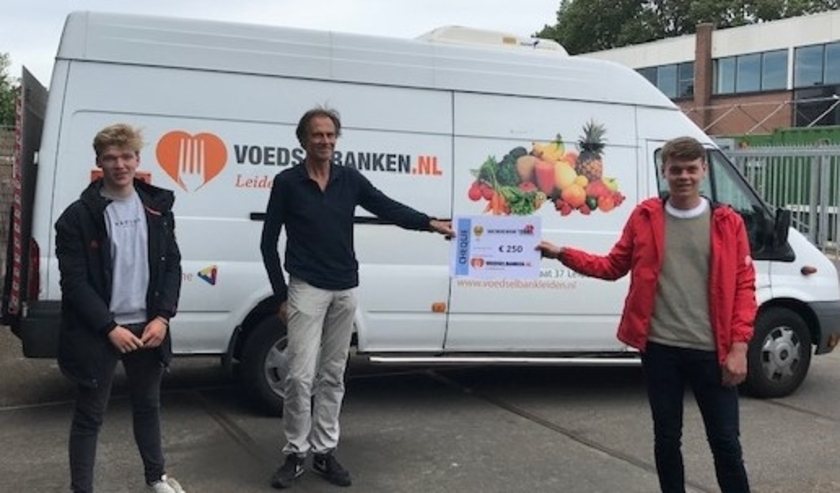 De coaches van Alecto JB1 overhandigden de cheque van 250 euro aan een vertegenwoordiger van de Voedselbank Leiden.