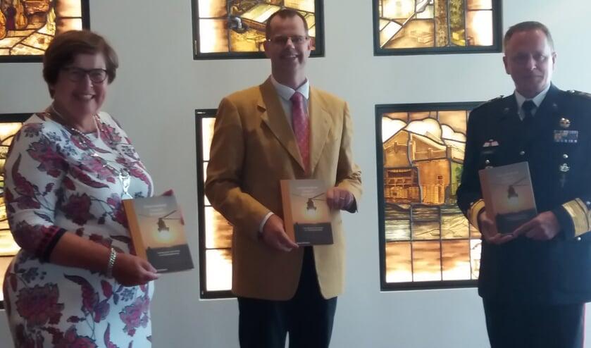 Auteur Joep Derksen reikt het Veteranenboek uit aan burgemeester Marina van der Velde en Inspecteur-Generaal der Krijgsmacht Frank van Sprang.
