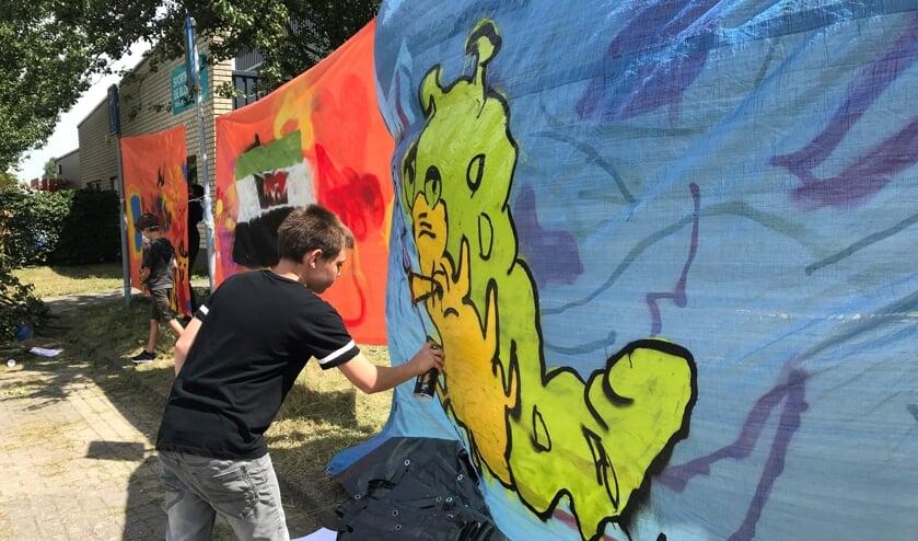Quinten werkt aan zijn graffiti kunstwerk.