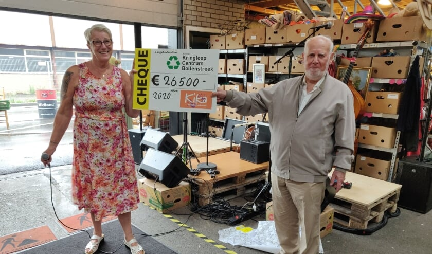Bedrijfsleidster Cathy en vrijwilliger Quirinus onthullen het bedrag voor KiKa.