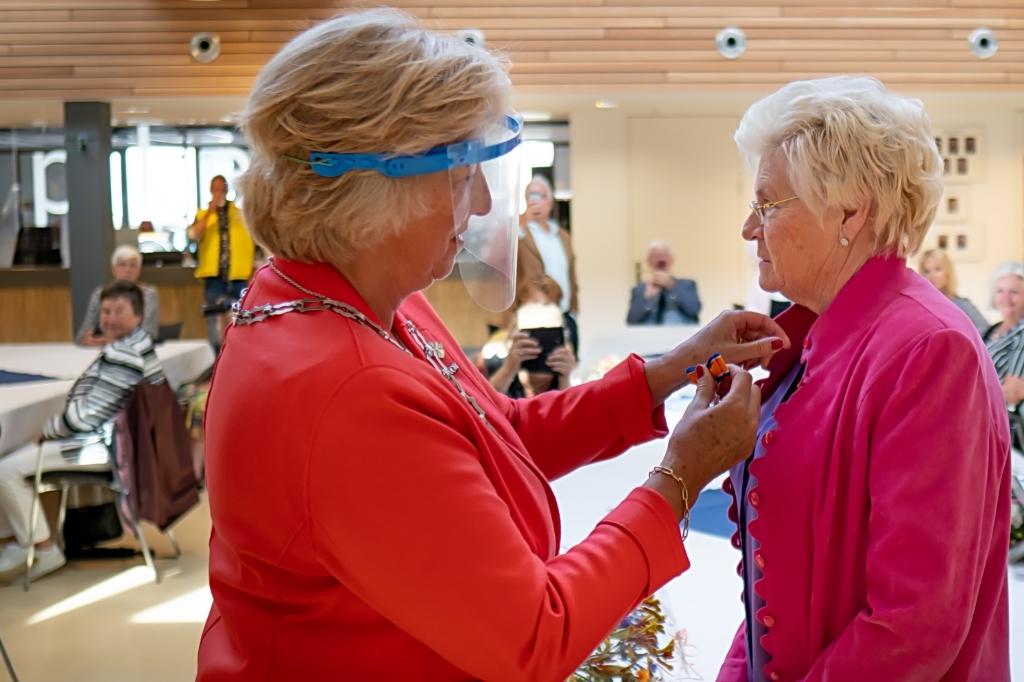 Burgemeester Driessen speldt het lintje op bij Beatrix Nieuwenhuis.  Foto: J.P.Kranenburg © uitgeverij Verhagen
