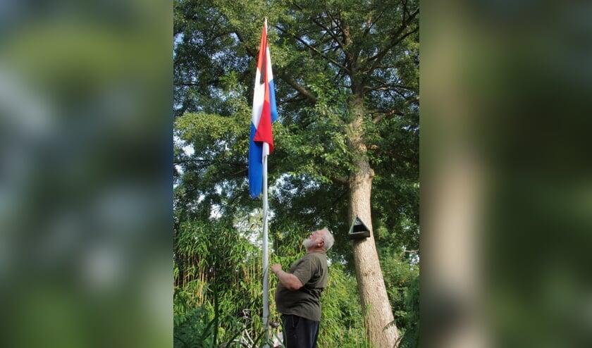 Dirk Megchelse bij zijn vlag met zwarte wimpel in de voortuin.   Foto Willemien Timmers