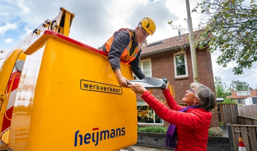 <p>Wethouder Hooij overhandigt symbolisch een armatuur aan de aannemer. | Foto: pr.</p>