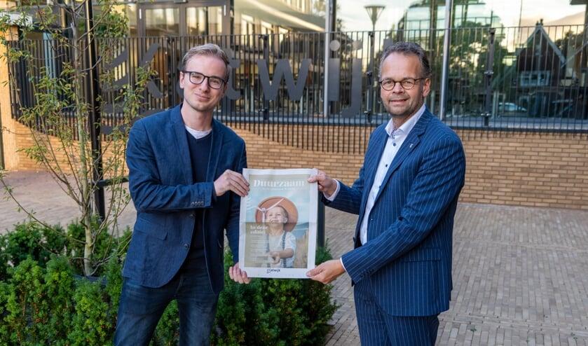 <p>Wethouder Jacco Knape(re) toont samen met beleidsmedewerker Steven van der Plas de Duurzaamheidskrant.&nbsp;</p>