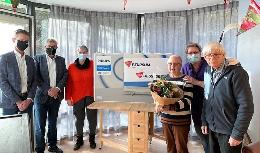 <p>Kees-Jan te Nijenhuis en Jan van Woerkom reiken de televisie uit aan Gonnie van Rijn.</p>