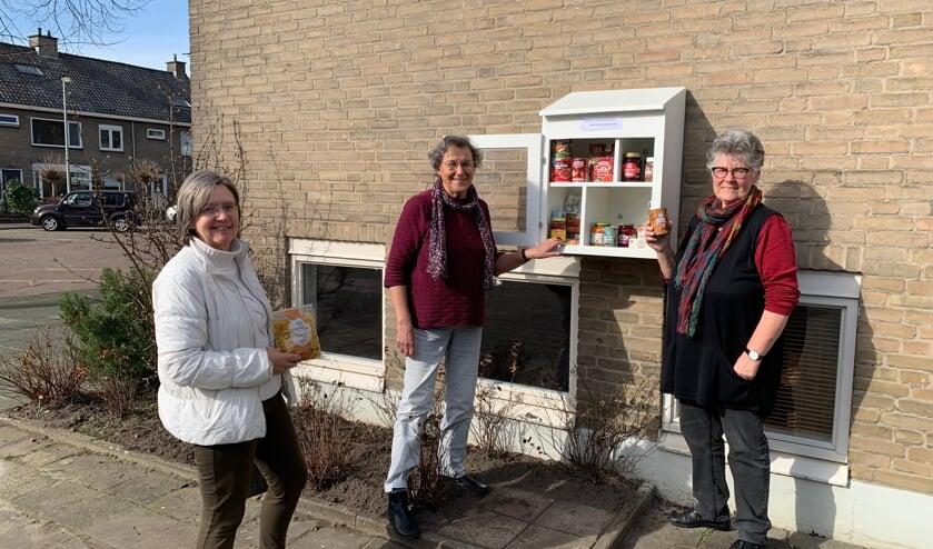 <p>V.l.n.r. Heleen Feenstra, Marijke van Pernis en Ellis Groothoff bij het buurtkastje aan het Burchtpad.</p>