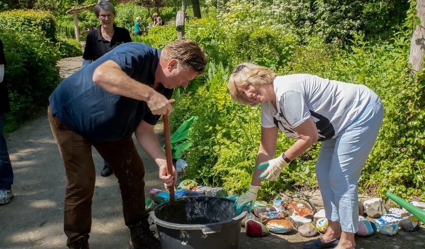 <p>Burgemeester Laila Driessen en wethouder Rik van Woudenberg plaatsten kleurrijke stenen langs het Verwonderpad. Op de achtergrond voorzitter Riny Vons van de Stichting Natuurspeeltuin Leiderdorp&nbsp;</p>