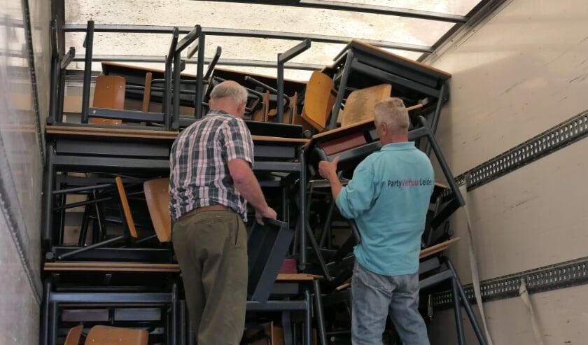 <p>Passen en meten om het schoolmeubilair in de vrachtwagen te krijgen.   Foto: Aart Broek</p>