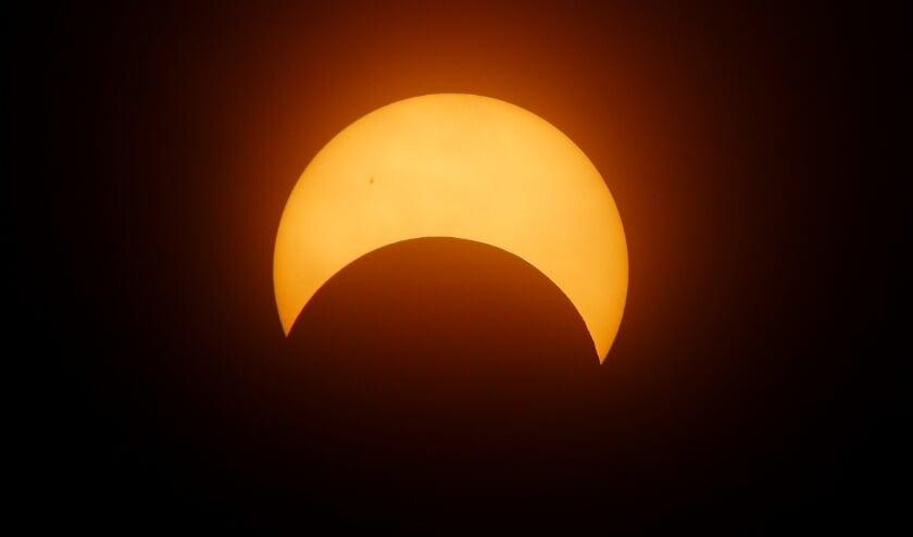 De maan dekt een deel van de zon af.