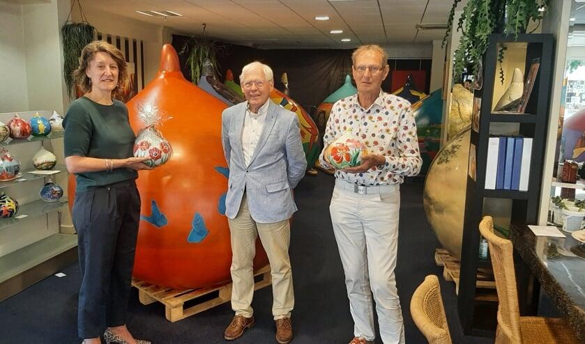 <p>Joost Paijmans, president van de Lions Lisse Oude Duinen, overhandigt de mini-bol aan de winnares Ivalda Booij. Rechts op de foto Jan van Vliet, trekker van het Reuzenbollen-project.</p>