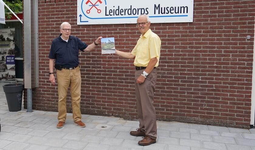 <p>Joop van Huut (rechts) overhandigt een foto van het naambord aan Bob Reidsma van het Leiderdorps Museum.&nbsp;</p>