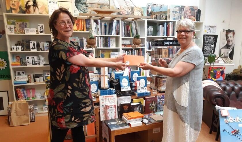 Sanne Boswinkel (links) ontvangt de boekenbon uit handen van Cadja van Rooden.
