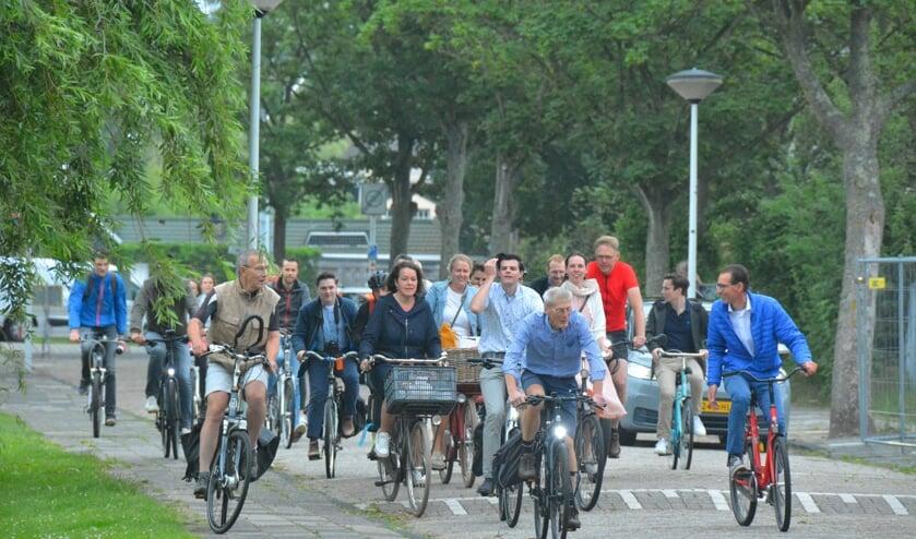 Collega's fietsen gezamenlijk een stukje op met hun directeur Geert Snoep.