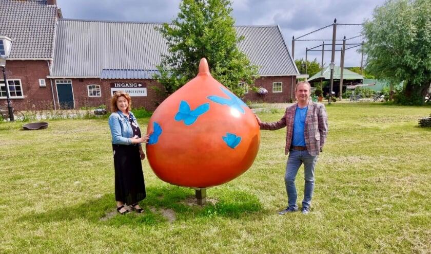 <p>Kunstenares Anita van Diemen en wethouder Jan van Rijn bij een van de twee reuzenbollen die in Hillegom staan. | Foto: Annemiek Cornelissen.</p>