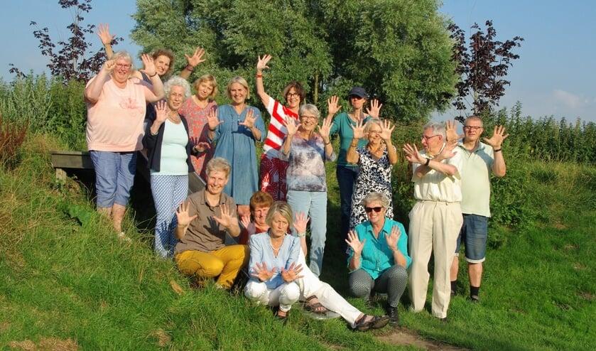 <p>Vijftien enthousiaste Wandelclub-deelnemers poseren voor een jubileumfoto in de zon. |</p>