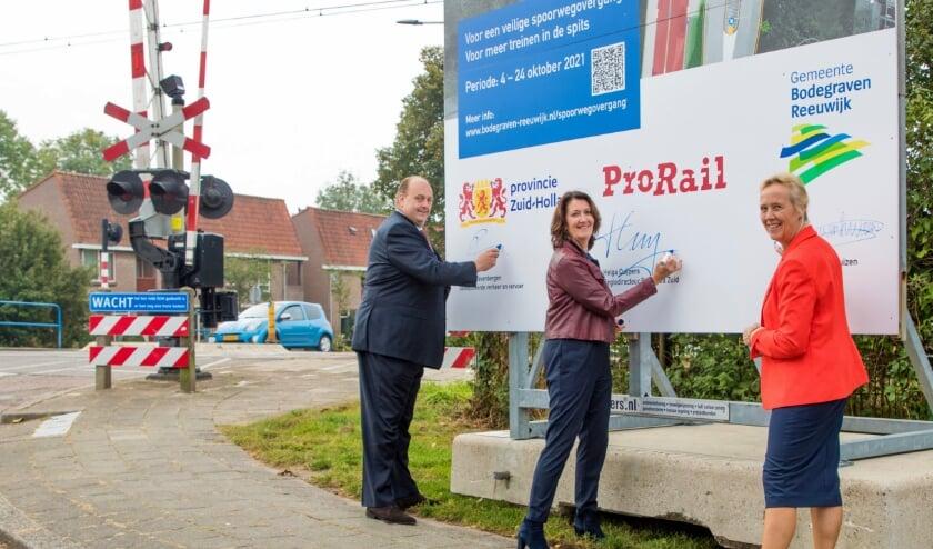 Met het zetten van een handtekening op een bouwbord bekrachtigden gedeputeerde Frederik Zevenbergen, wethouder Inge Nieuwenhuizen van Bodegraven-Reeuwijk en ProRail regiodirecteur Helga Cuijpers op vrijdag 24 september 2021 de samenwerking.