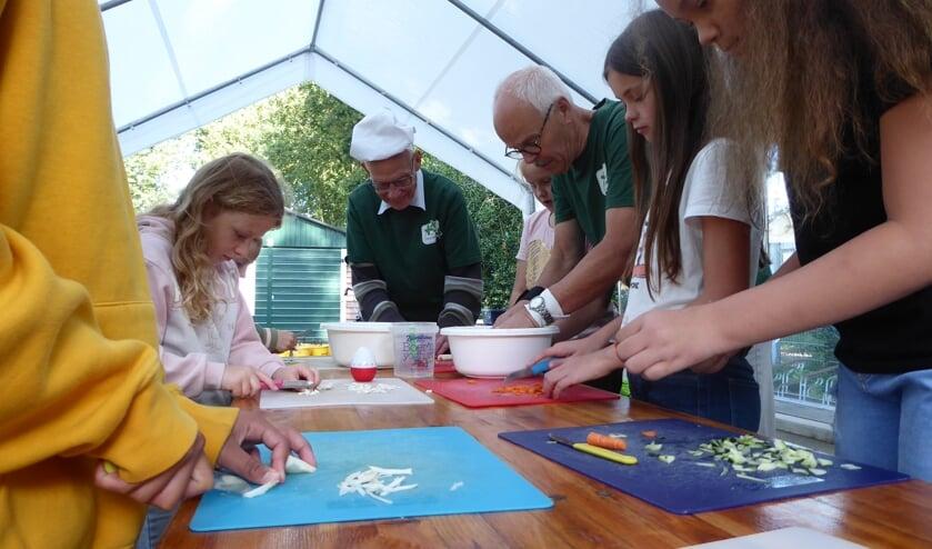 Leerlingen van de Regenboogschool snijden de groente met hulp van vrijwilligers.