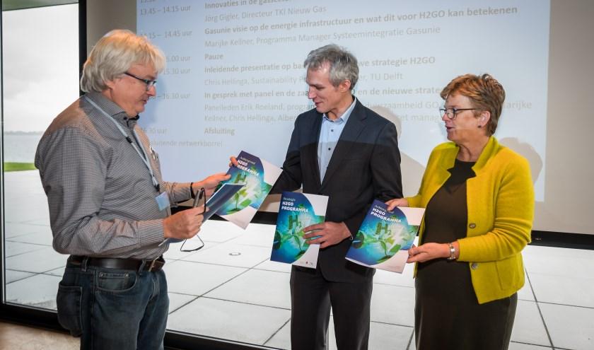 Chris Hellinga (TU Delft), schrijver van de strategie, overhandigt de strategie aan Tea Both van de gemeente Goeree-Overflakkee en gedeputeerde Berend Potjer van de provincie Zuid-Holland