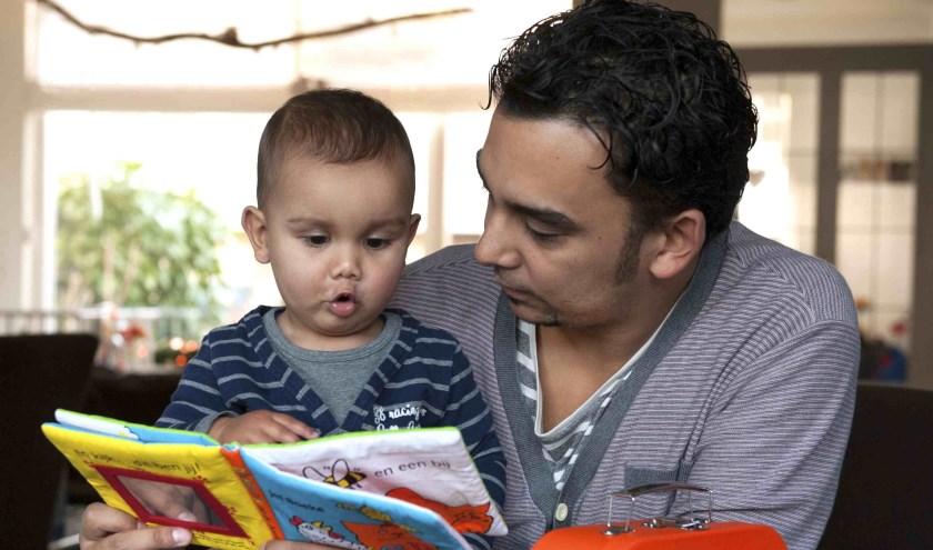 Foto van een vader die een boekje leest met zijn zoontje
