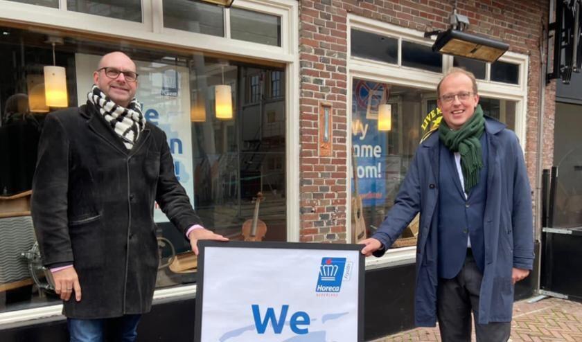 KHN Friesland-voorzitter Ton Eijer (links) overhandigt Leeuwarder wethouder Fruiso Douwstra een symbool van de actie.