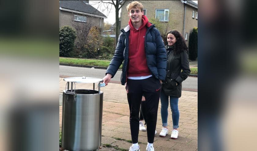 Een leerling van het Marne College deponeert zijn mondkapje in een afvalbak.