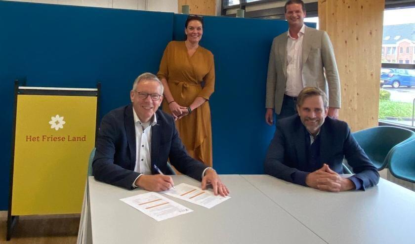 Klaas Kuilman, directeur van Thuiszorg Het Friese Land (zittend links), en Erik Wijnhof, directeur van Zorgcentrale Noord (zittend rechts) ondertekenen het nieuw contract, Ypie Duursma-Groenewoud van Thuiszorg Het Friese Land en Maarten den Heijer van Zorgcentrale Noord kijken toe.