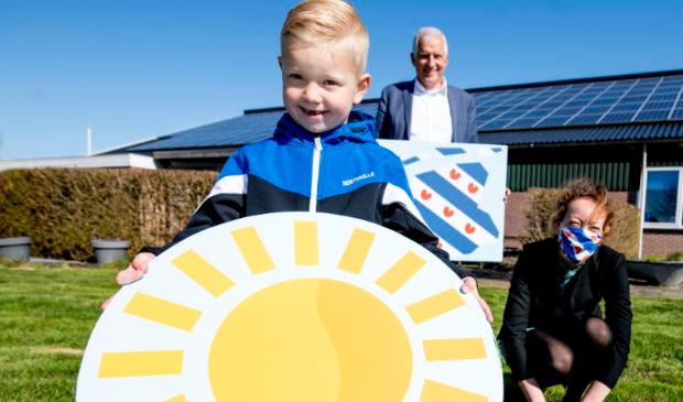 Gedeputeerde Sietske Poepjes en wethouder Bert Wassink overhandigen Jelte met de symbolische zon een duurzame toekomst in Fryslân toe.
