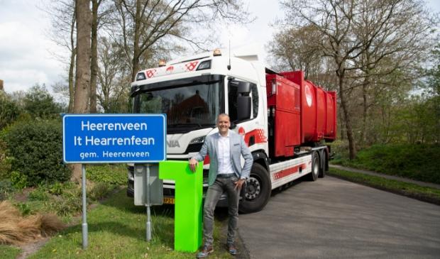 <p>Wethouder Jaap van Veen poseert samen met een Omrin-vuilniswagen bij een bord van Heerenveen.</p>
