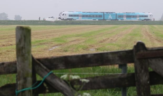 <p>De trein, met het doek dat door de brandweer om de auto is gespannen zodat de privacy gewaarborgd is van de twee omgekomen personen.</p>