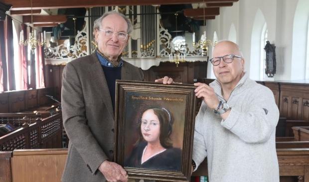 <p>Arthur Oster (links) reikt het schilderij uit aan Henny Boon von Ochsee, die de kerk van Wiuwert vertegenwoordigd.</p>