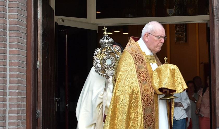 In processie werden kerkelijke attributen naar de nabij gelegen Odulphuskerk gebracht. Daar worden ze bewaard. Foto: Marijke Vermeulen