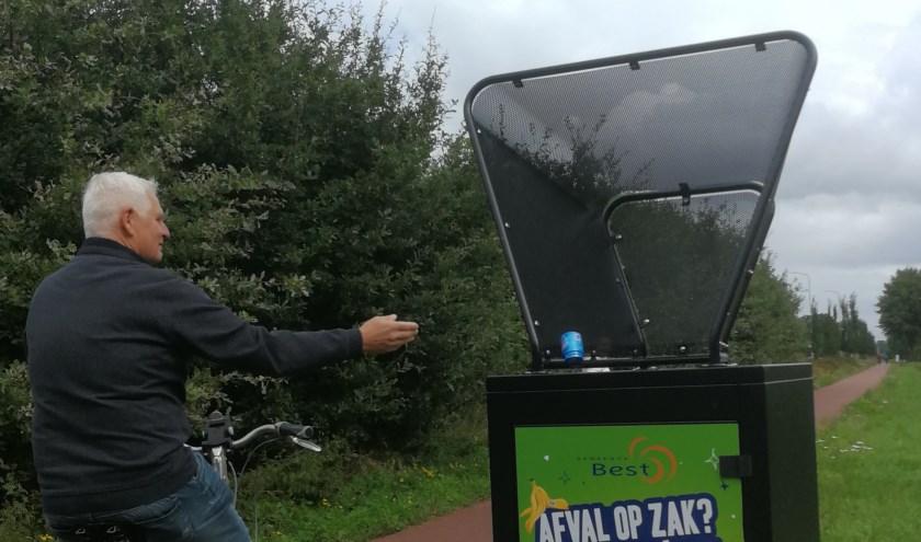 Wethouder Rik Dijkhoff werpt vanaf de fiets een blikje in de vanger.