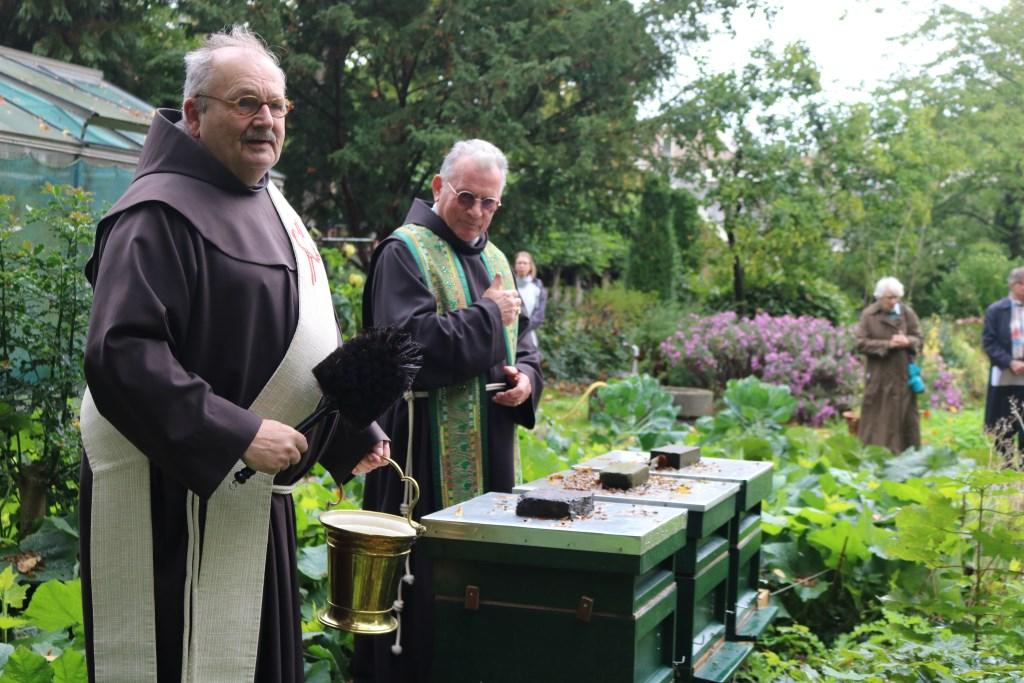 """Gardiaan Wim van Bemmel (rechts) en Jan Bouwens zegenen de bijen. """"Dat we lekkere honing van ze mogen krijgen"""".  © bosscheomroep.nl"""