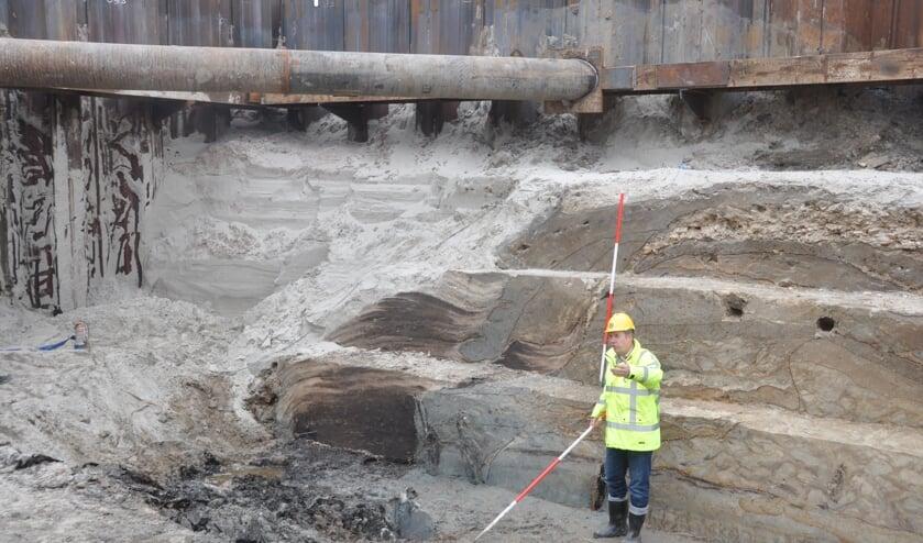 Archeoloog Michiel Bartels laat de restanten van de oude dijk in de huidige Waddenzeedijk bij De Schans zien.