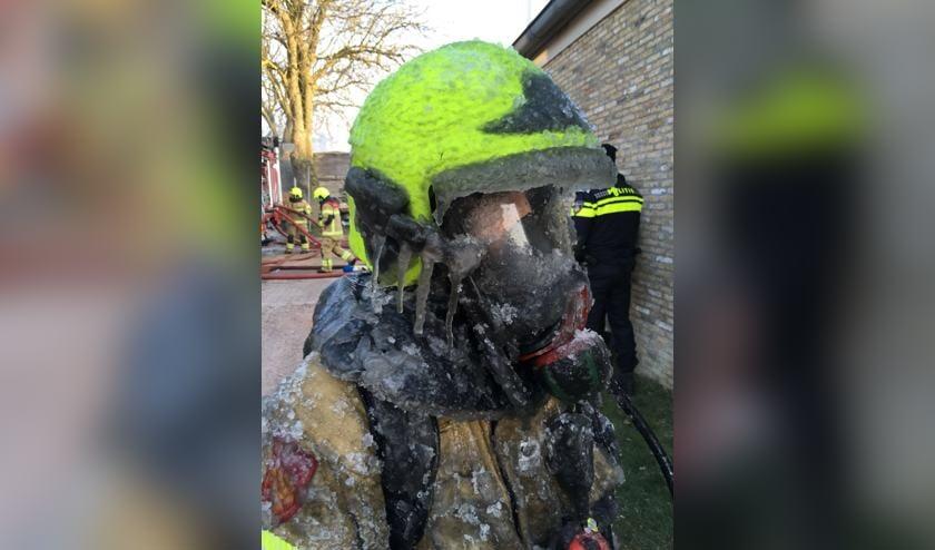 IJspegels aan de helm van de brandweer na het blussen in Oosterend.