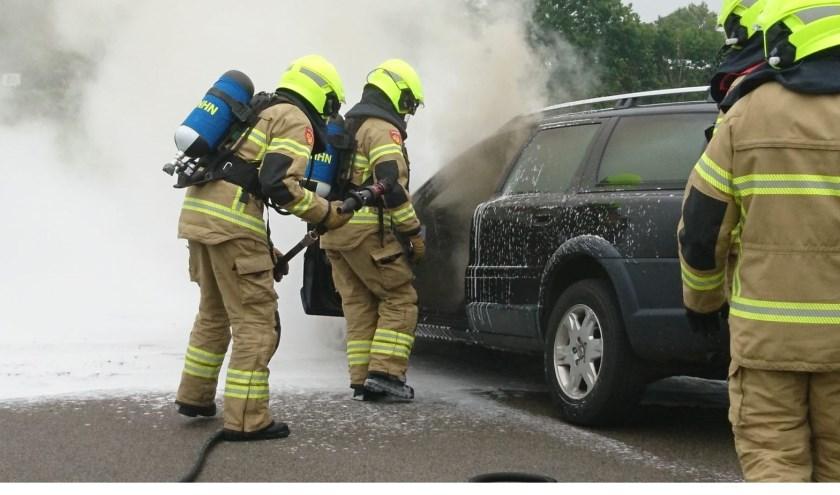 Brandweerlieden blussen de autobrand.  Foto Inter Visual Studio / Marcel Winter