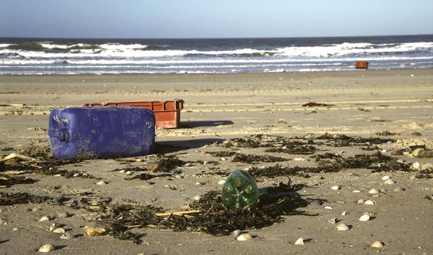 <p>Zwerfvuil op strand plastic krat en vat</p>