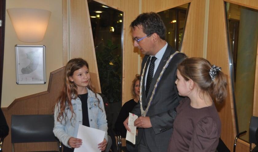 Bloem van der Velde en Rianne Witte overhandigen de handtekeningen aan burgemeester Uitdehaag.