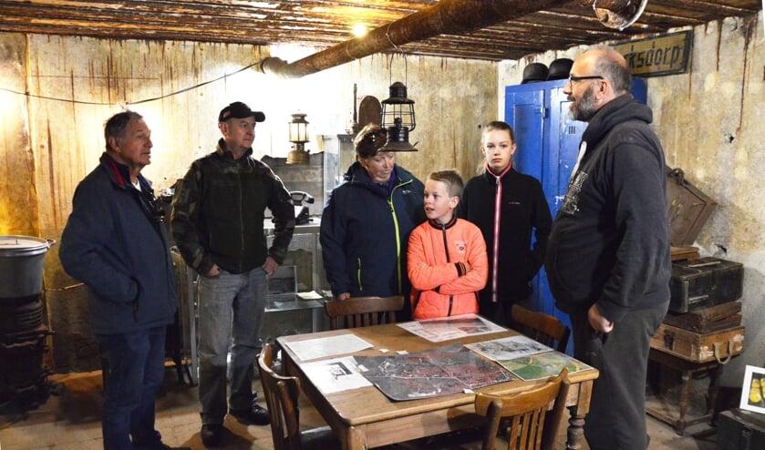 Vrijwilligers Pieter-Jan Kampstra (rechts) en Harry Kingma (tweede van links) geven bezoekers uitleg in de bunker.
