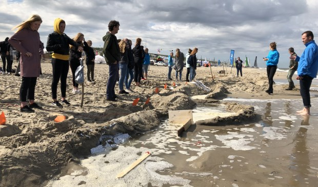 Testen van de zelfgebouwde dijken op het strand.