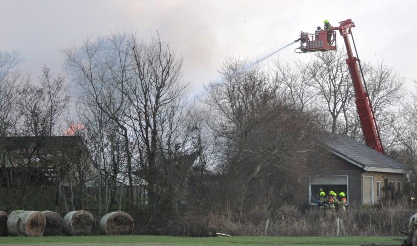 Met behulp van de hoogwerker werd de brand in de schuren bestreden.