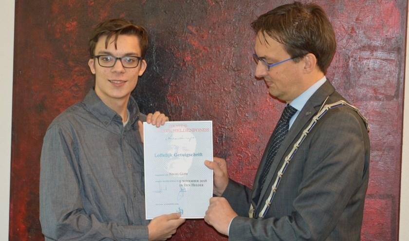 Burgemeester Uitdehaag overhandigt het getuigschrift van het Carnegie Heldenfonds aan Nigel Tervoort.