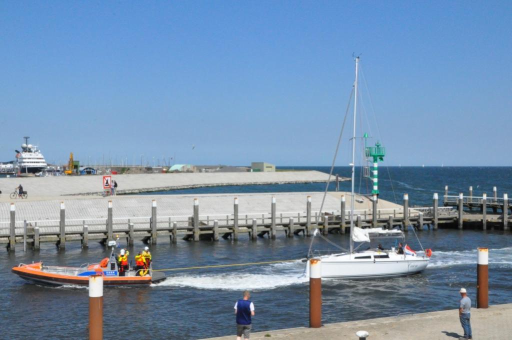 De Cornelis Dito sleept het jacht de haven in.